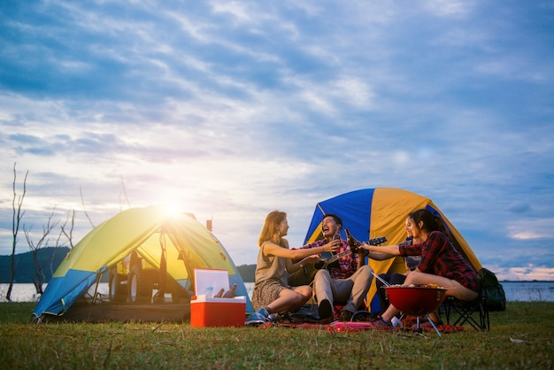 Group of man and woman enjoy camping picnic and barbecue at lake with tents in background. young mixed race asian woman and man. young people's hands toasting and cheering bottles of beer. Free Photo