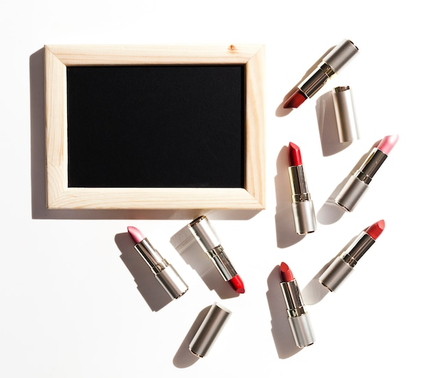 Group of metallic lipsticks with blackboard Free Photo