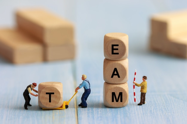 Group of miniature people assemble wooden cube, team support and help concept. business teamwork concept. Premium Photo