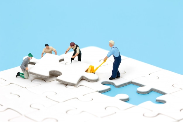 Group of miniature people assembling jigsaw puzzle. business teamwork concept. Premium Photo