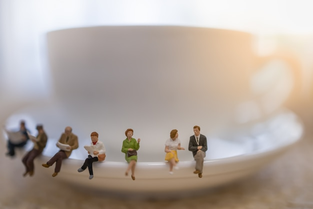 Group of miniature people figures sitting, talking, waiting and reading newspaper and book on white plate Premium Photo