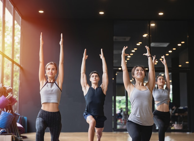 Group of mix race people practicing yoga meditating together for healthy lifestyle in fitness club Premium Photo