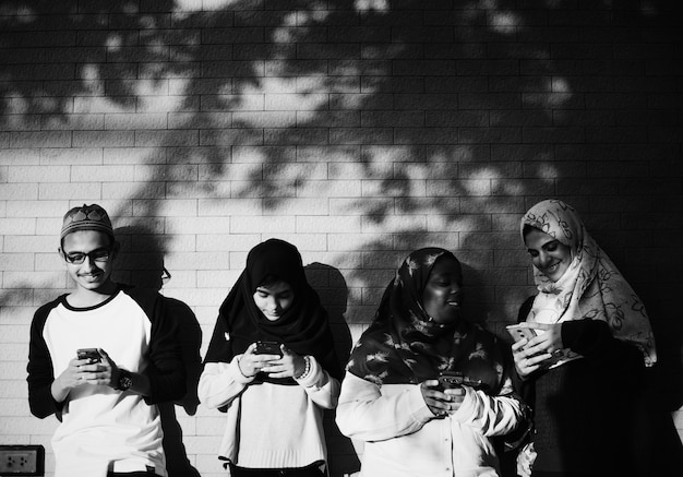 A group of muslim students using mobile phones Free Photo