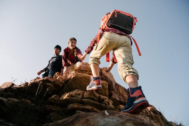 Группа в составе туризм азии помогает силуэту друг друга в горах с солнечным светом. Premium Фотографии