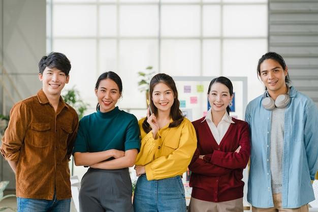 Группа молодых творческих людей азии в смарт-повседневной одежде улыбается и скрещенными руками в творческом офисе на рабочем месте. разнообразные азиатские мужчины и женщины выступают вместе при запуске. концепция совместной работы коллег. Бесплатные Фотографии