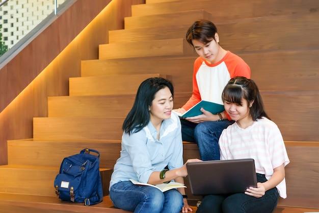 図書館の階段の背景に座っている間、講師とノートパソコンの教授法レッスンを使用しているアジアの学生のグループ Premium写真