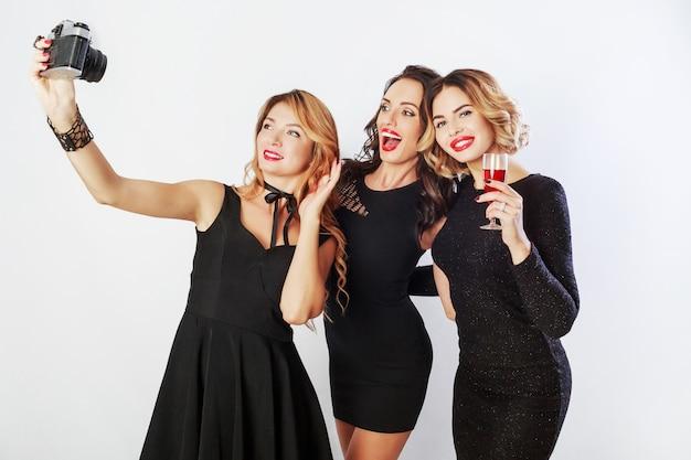 Группа лучших друзей, три элегантные девушки в черном роскошном платье делают автопортрет, пьют красное вино, позируют. Бесплатные Фотографии