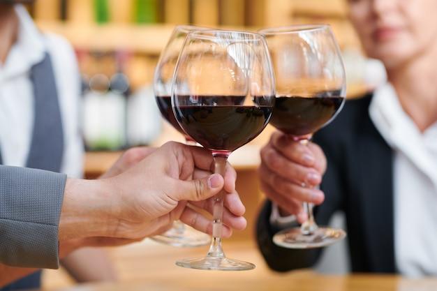 Группа деловых людей поздравляет друг друга с успешной сделкой, чокаясь бокалами вина бордо Premium Фотографии