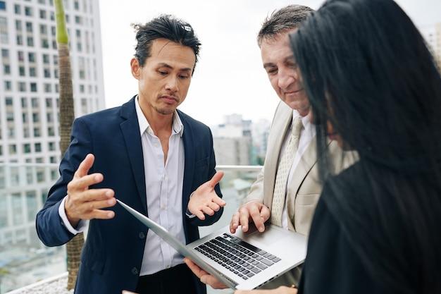 建物の屋上で会議をするときにノートパソコンの画面でのプレゼンテーションについて話し合うビジネスマンのグループ Premium写真