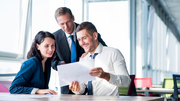 Group of businesspeople looking at business plan in the office Free Photo