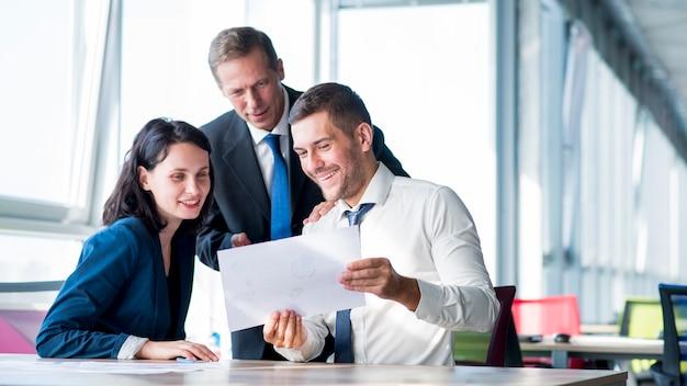 オフィスでビジネスプランを見ているビジネスマンのグループ Premium写真