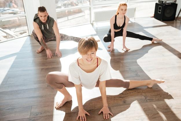 Группа веселых молодых людей, практикующих йогу с тренером Premium Фотографии