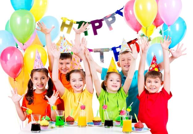 挙手で誕生日パーティーでカラフルなシャツを着た子供たちのグループ-白で隔離 無料写真