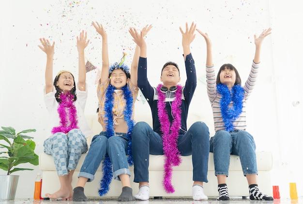 Группа детей играть с воздушными шарами, конфетти в светлой комнате на вечеринке, концепция счастливого детства Premium Фотографии