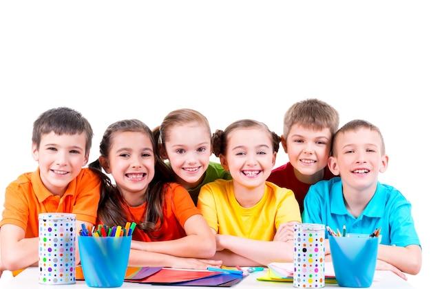 マーカー、クレヨン、色付きの段ボールでテーブルに座っている子供たちのグループ。 無料写真