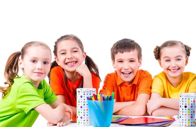 Группа детей, сидящих за столом с фломастерами, мелками и цветным картоном Бесплатные Фотографии