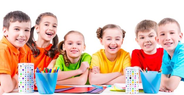 Группа детей, сидящих за столом с фломастерами, мелками и цветным картоном. Бесплатные Фотографии