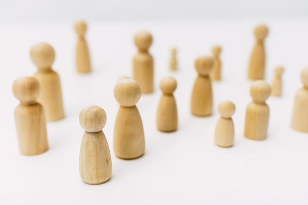 白い背景のスタジオで分離された木製の数字で表される混乱のグループ化された人々のグループ。 Premium写真