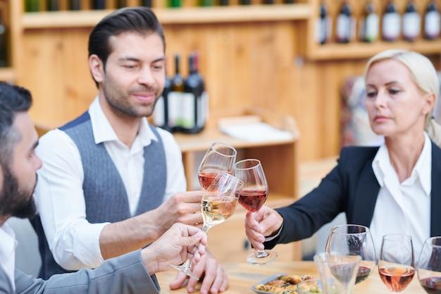 Группа современных виноделов, чокающихся за столом бокалами с различными сортами вина, работая в погребе Premium Фотографии