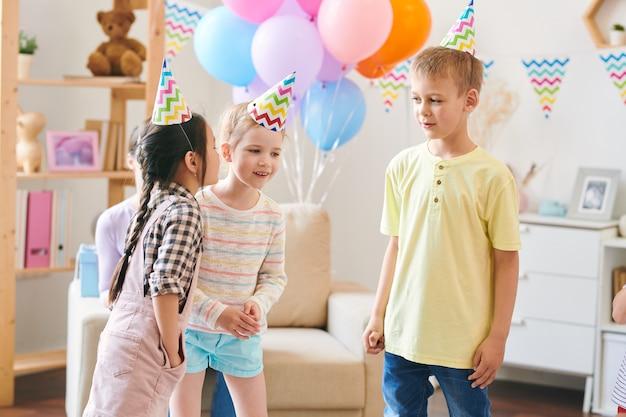 飾られた部屋でホームパーティーで楽しみながら新しいゲームのルールを議論する誕生日キャップのかわいい子供たちのグループ Premium写真