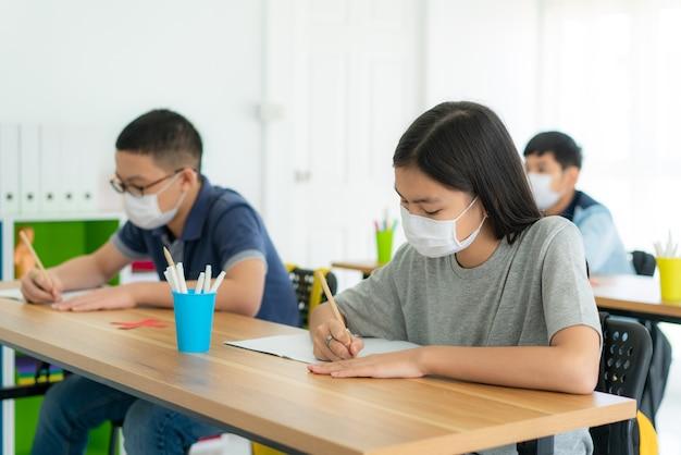 教室で衛生的なマスクを着ている小学生のグループ Premium写真