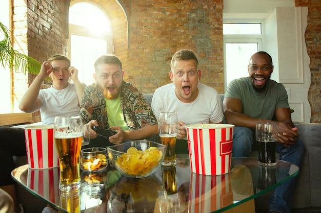 家でビデオゲームをしている興奮した友人のグループ。男性ゲーマーやファンが家で一緒に時間を過ごして楽しんでいる 無料写真