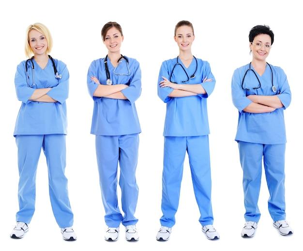 白で隔離の青い制服を着た4人の陽気な女性医師のグループ 無料写真