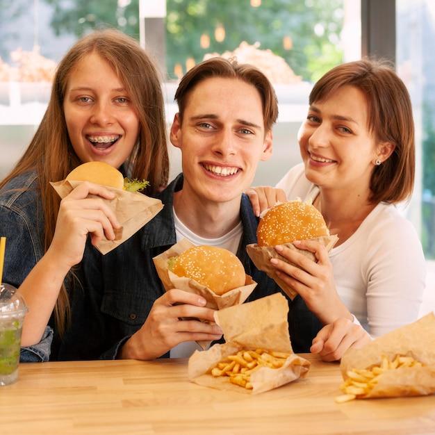 Группа друзей в ресторане быстрого питания, едят гамбургеры Бесплатные Фотографии