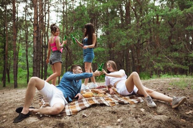 夏の森でのピクニック中にビール瓶をチャリンと友人のグループ。ライフスタイル、友情 無料写真