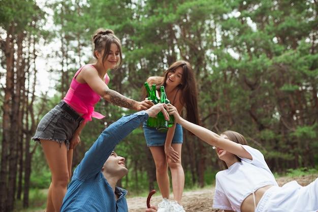 夏の森でのピクニック中にビール瓶をチリンと友人のグループ 無料写真