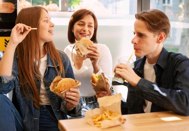 Группа друзей, вместе едят фаст-фуд Бесплатные Фотографии