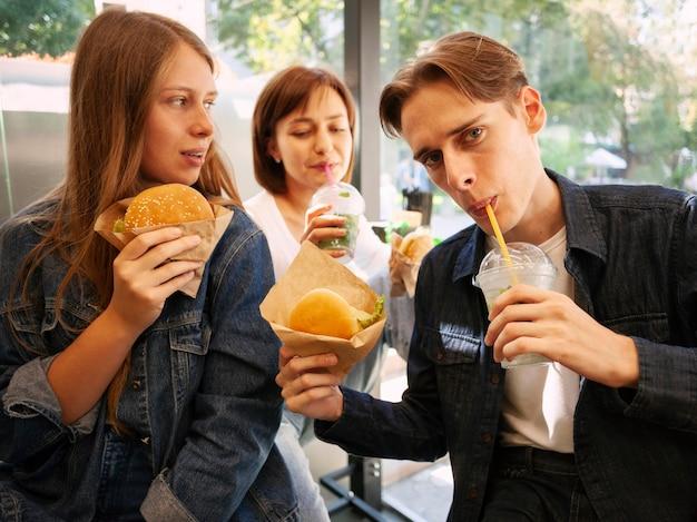 ファーストフードを食べる友人のグループ 無料写真