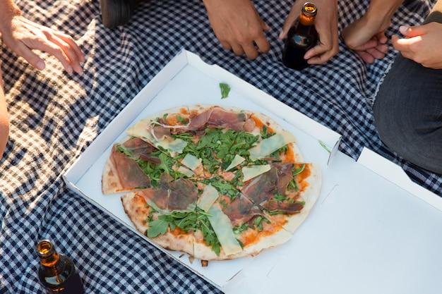 Группа друзей, едят пиццу на открытом воздухе Бесплатные Фотографии