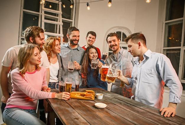 Группа друзей, наслаждаясь вечерними напитками с пивом на деревянный стол Бесплатные Фотографии