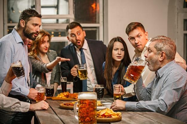 Группа друзей, наслаждаясь вечерними напитками с пивом на деревянном столе Бесплатные Фотографии