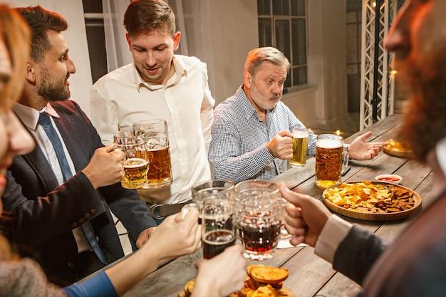 Группа друзей, наслаждающихся вечерними напитками с пивом Бесплатные Фотографии