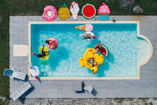 さまざまなエアベッドのあるプールで楽しんでいる友人のグループ Premium写真