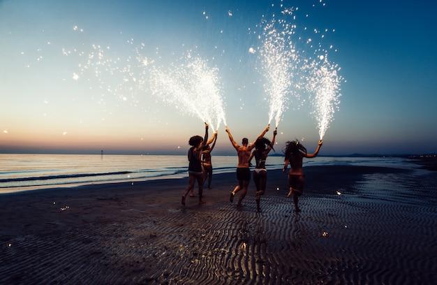 Группа друзей весело бегать по пляжу с бенгальскими огнями Premium Фотографии