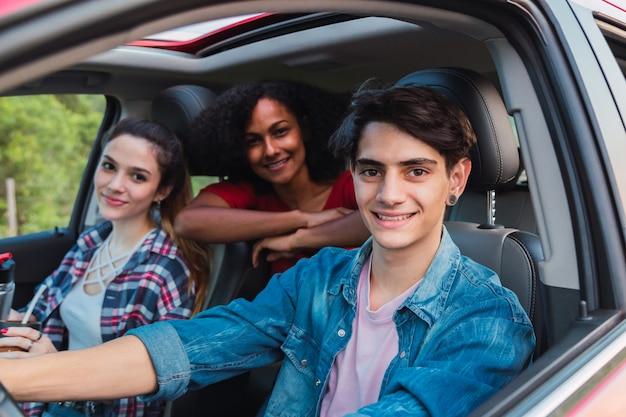 Группа друзей смотрит в окно проезжающей машины Premium Фотографии