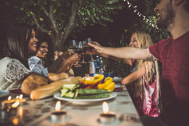 夕食時に裏庭でバーベキューを作る友人のグループ Premium写真