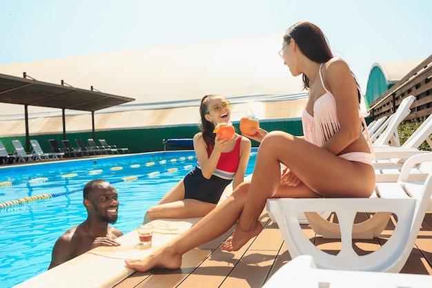 Группа друзей, играющих и отдыхающих в бассейне во время летних каникул Бесплатные Фотографии