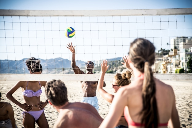 Группа в составе друзья играя пляжный волейбол на пляже. Premium Фотографии