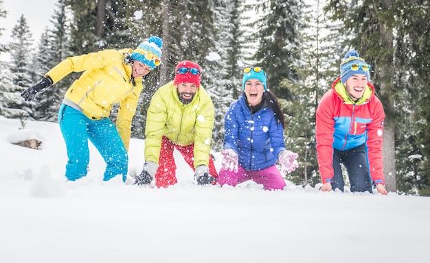 Группа друзей, играющих в снегу Premium Фотографии