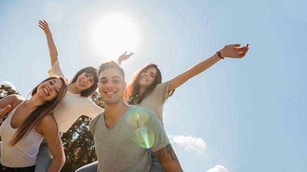 하늘 배경에 팔을 올리는 친구의 그룹 프리미엄 사진