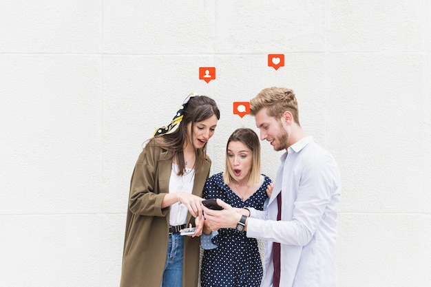 Group of friends standing near the wall texting on mobile phone Free Photo