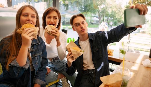 ファーストフードを食べながら自分撮りをしている友人のグループ 無料写真