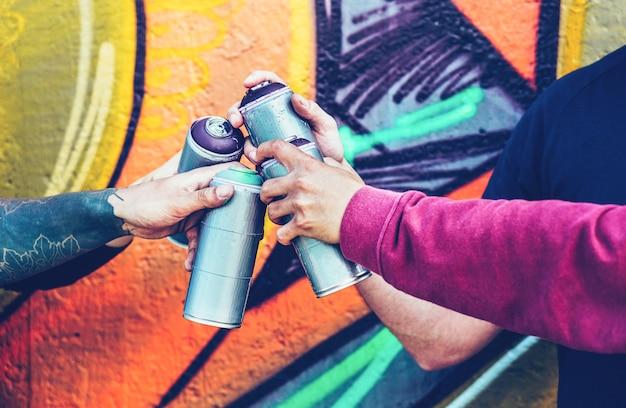 스프레이 컬러 캔을 잡고 손을 쌓아 낙서 예술가의 그룹 프리미엄 사진