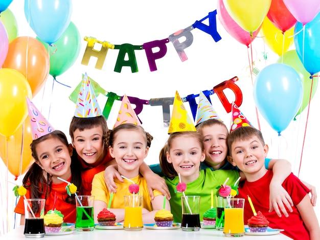 誕生日パーティーで楽しんでいるカラフルなシャツを着た幸せな子供たちのグループ-白で隔離 無料写真