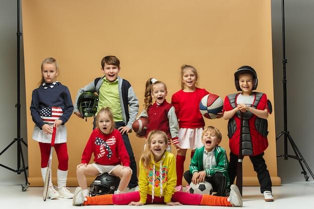 幸せな子供たちのグループは、さまざまなスポーツを示しています。 無料写真