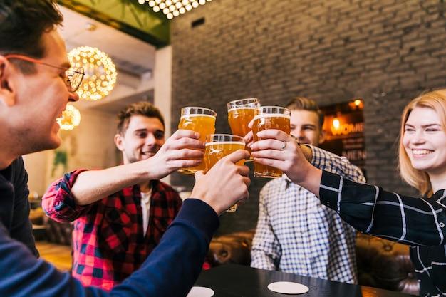Группа счастливых друзей, аплодисменты с пивные бокалы Premium Фотографии
